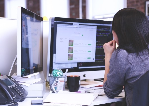 woman working at computer with two screens