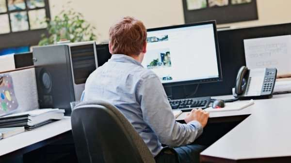 man at desk work on computer with large monitor