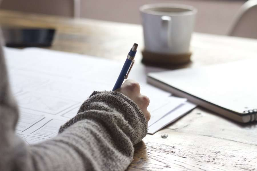 woman writing on desk with coffee mug