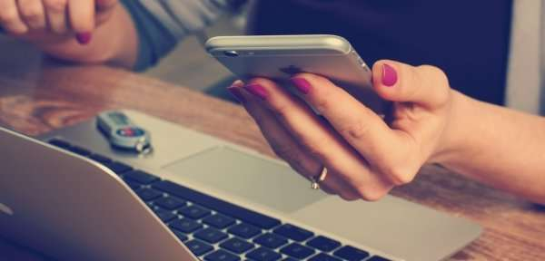 woman holding an iphone at a laptop