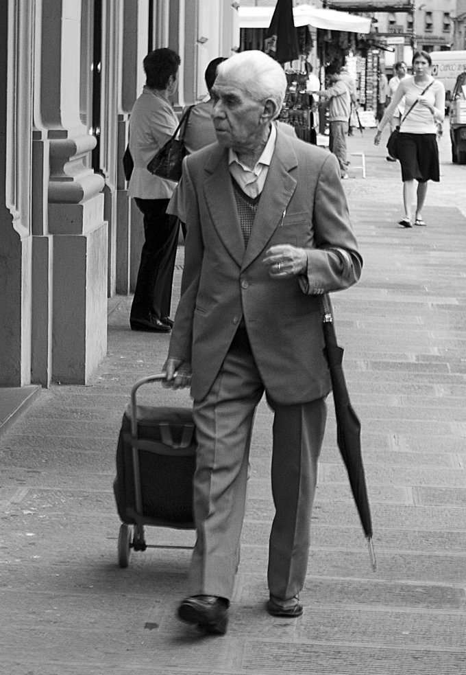 older man on the street with an umbrella