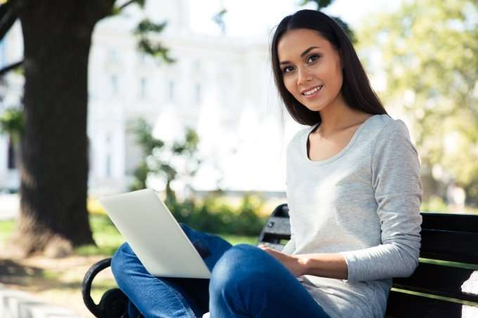 woman working at laptop on park bench