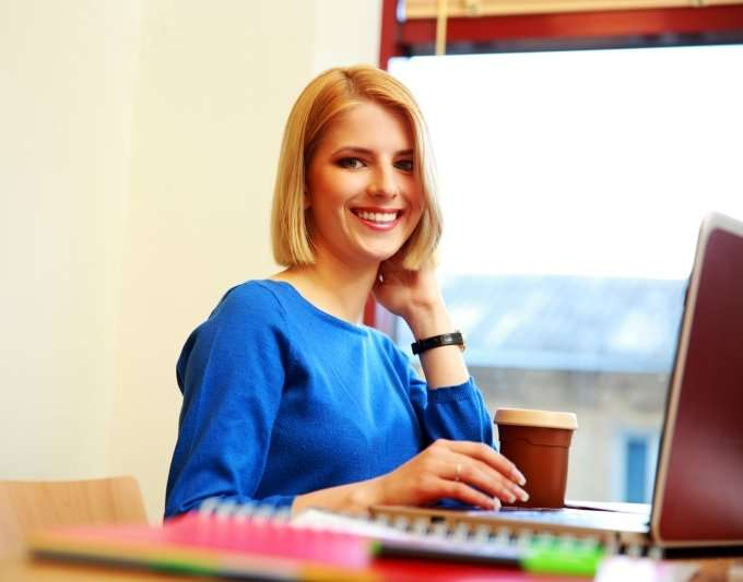 blonde woman at laptop in front of window
