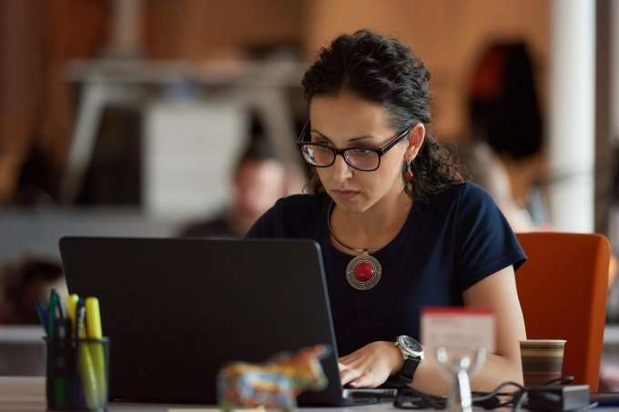 woman with glasses working at a laptop