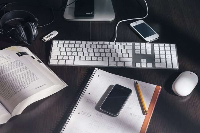 desk with books, computer and smart phone
