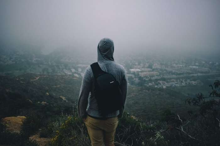 hooded man with backpack looking over horizon