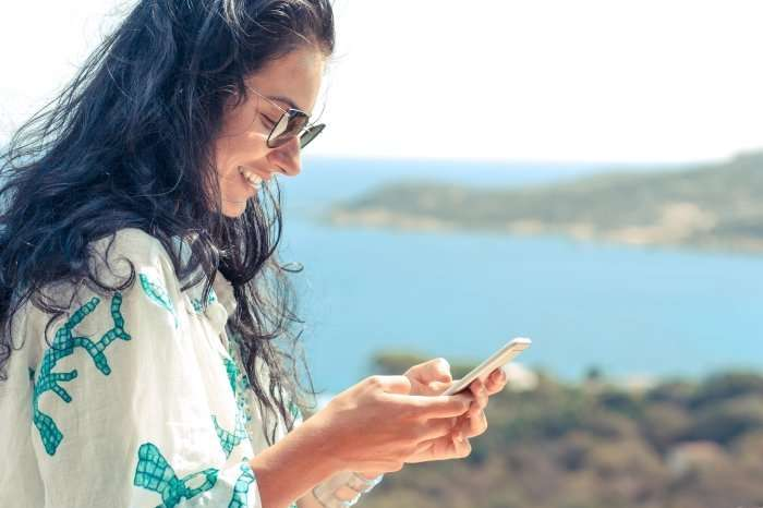 woman on smart phone with bay in background