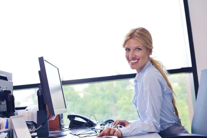 woman working at a computer in front of a window