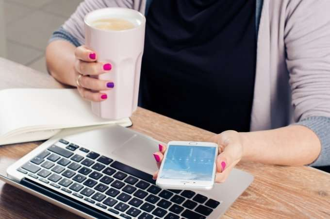 woman-with-cup-of-coffee-smart-phone-and-laptop-with-one-finger-with-different-nailpolish