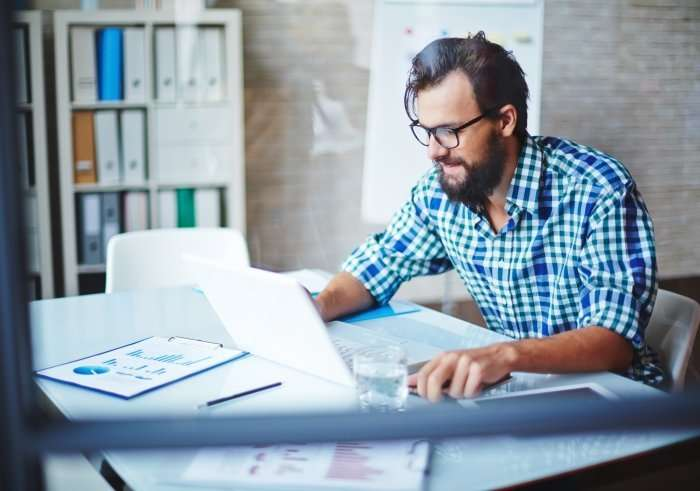 Man with beard working at laptop