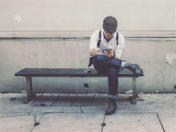 man on bench on his phone