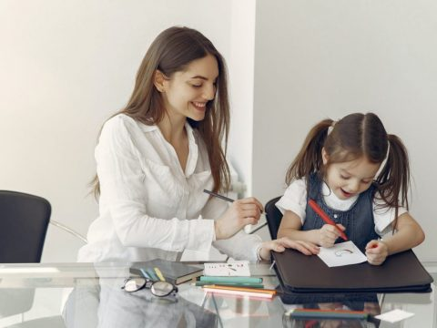 young woman tutoring little girl in office
